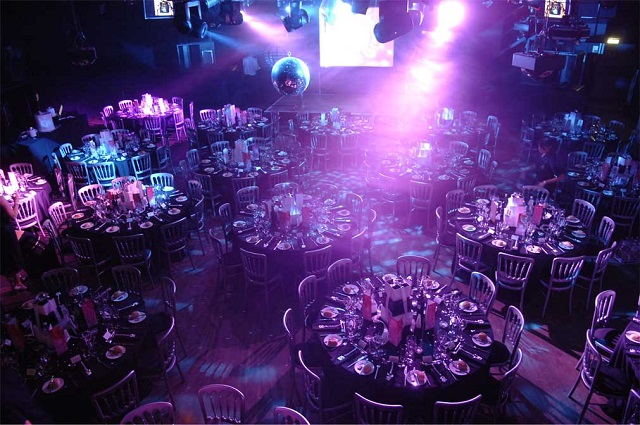 Round tabkes set up for seated dinner in large room. Ministry Of Sound Christmas Party SE1