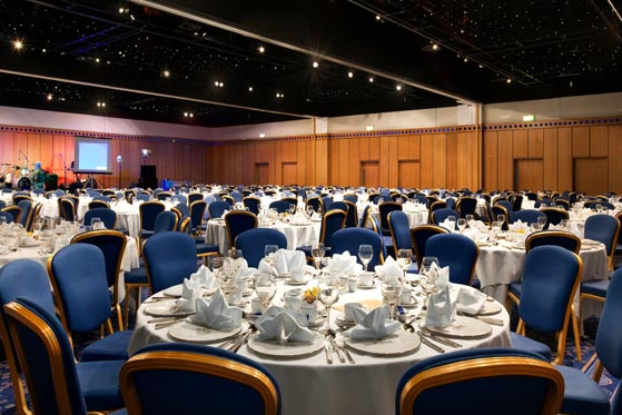 Gateshead Suite set for a large Christmas party with round tables dressed in white linen and place settings with delicately folded napkins Hilton Newcastle Gateshead Christmas Party NE8