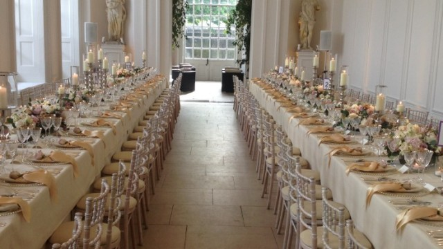 Orangery set for a banquet with 2 large long tables either side of each other with views to the grand entrance to the space Kensington Palace Venue Hire W8