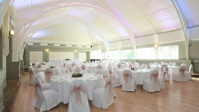 Terrace Suite set up for a wedding with lots of natural daylight and white table linen with matching chair covers with bows Birmingham Botanical Gardens Summer Party B15