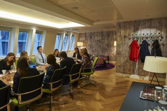 Quirky meeting room with slanted roof and abundance of natural daylight through slanted windows. Delegates host a meeting boardroom style with coats hung up Drawing Room 8 Fenchurch Place Venue Hire EC3
