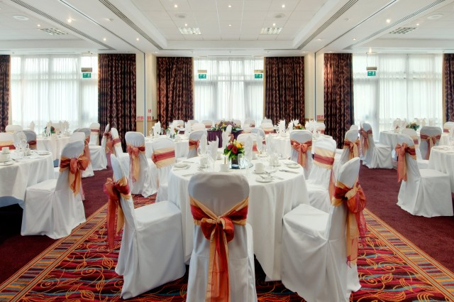 Invicta Suite set up for a christmas party with round tables dressed in white table linen with chair covers with bows and natural daylight into the roomHilton Maidstone Christmas Party ME14