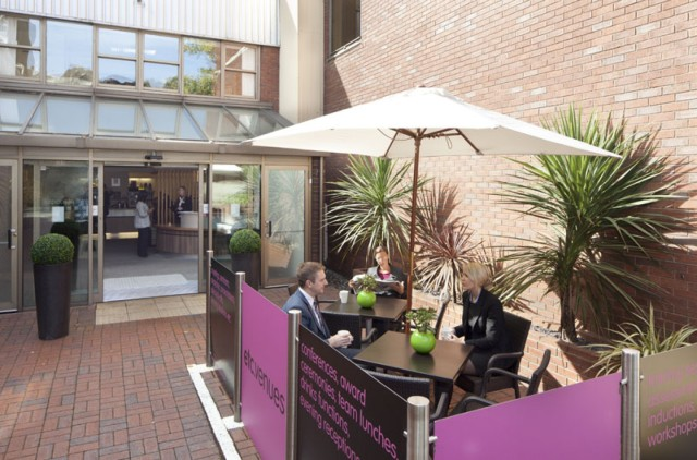 Outside Area with plants seating area and parasol outside reception for guests to enjoy Avonmouth House Venue Hire SE1