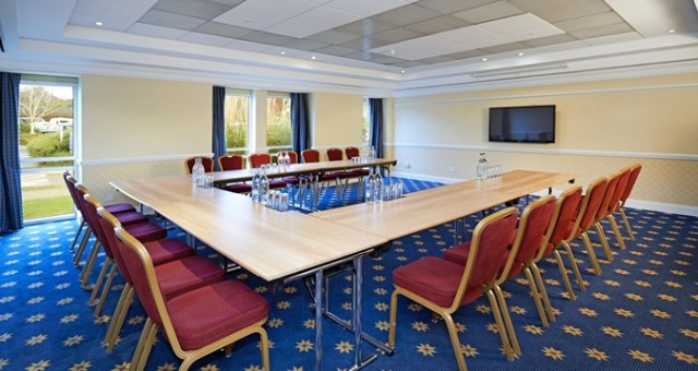Aylesford Suite set for a meeting with tables set in a u-shape with natural daylight and tv screen on the wall Hilton Maidstone Venue Hire ME14