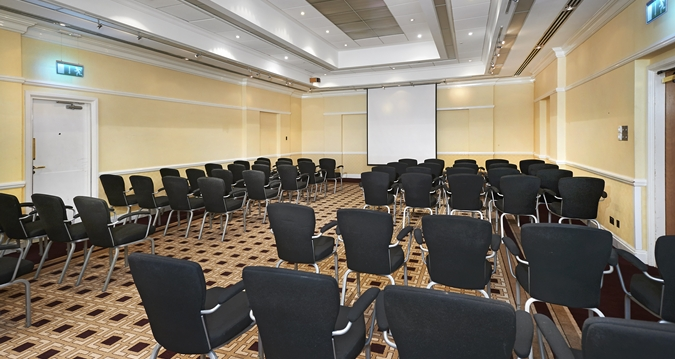 Bearsted Suite set in theatre style with chairs facing the projector screen at the front on the room with high ceilings and up lighters built into the ceiling for extra light Hilton Maidstone Venue Hire ME14