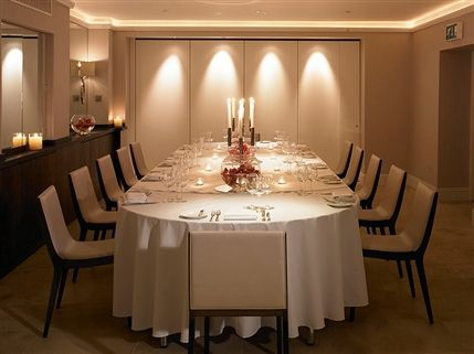 Garden Room 1 set for a dinner with white linen and floral centre pieces with wall partition Bingham Hotel Christmas Party TW10