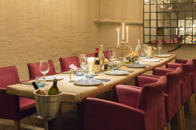 Anthologist Christmas Party EC2. Private room with white exposed brickwork with large dining room with red chairs, candle in centre of table with lovely furnishings.