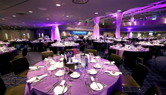 Bobby Moore Room set for a dinner party with uplighters around the room and round tables dressed in table linen with place settings Wembley Stadium Venue Hire HA9
