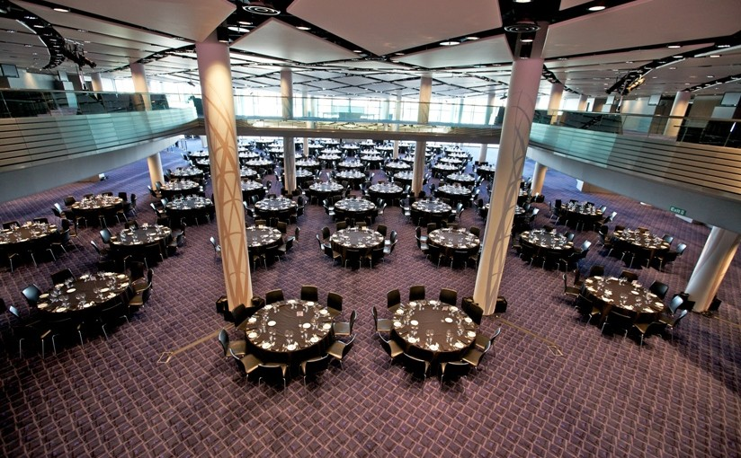 Bobby Moore Room set for a large conference with tables set in cabaret style with natural daylight and 2 large pillars in the centre of the room Wembley Stadium Venue Hire HA9