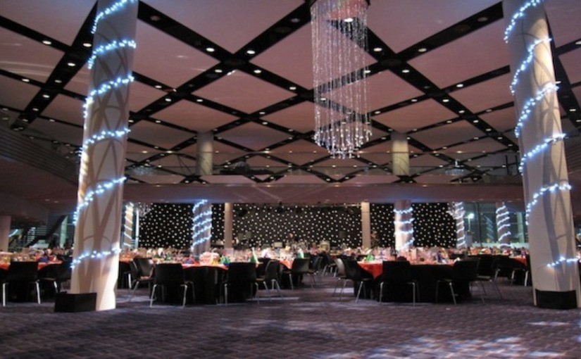 Bobby Moore Room set for a large Christmas party with tables set in cabaret style with natural daylight and 2 large pillars in the centre of the room wrapped with fairy lights and long chandelier hanging from the grand ceiling Wembley Stadium Christmas Party HA9