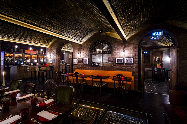 Copa de Cava underground private room with exposed brick work and bright coloured seating and private bar Camino Blackfriars Christmas Party EC4
