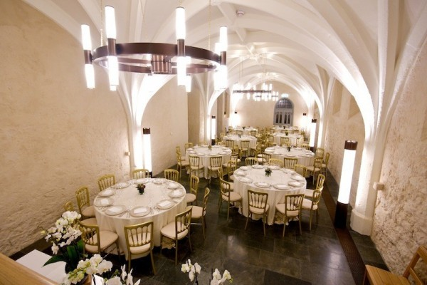 Cellarium set for a dinner with round tables dressed in white table line and high arched stone ceilings Westminster Abbey Christmas Party SW1