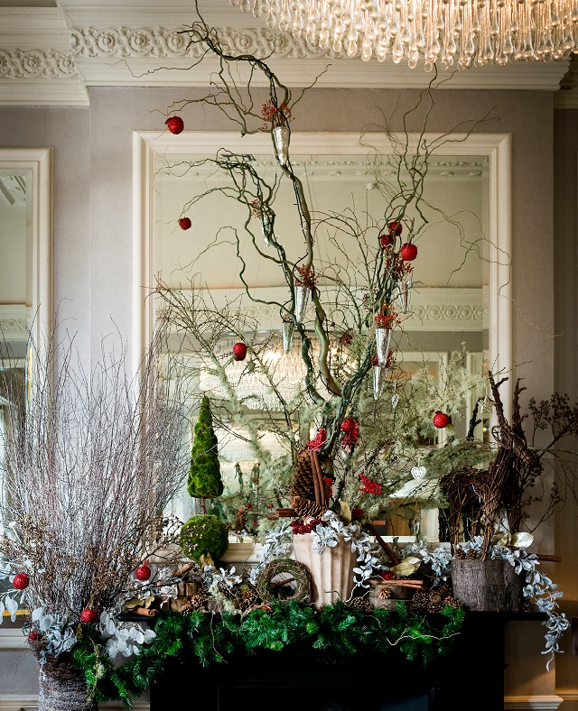 Christmas Bar with green foliage and red baubles hanging from twigs and branches Arrangement Bingham Hotel Christmas Party TW10