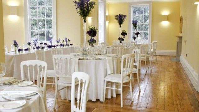 Drawing Room set for a formal dinner with large floral centre pieces on small round tables and natural daylight Clissold House Venue Hire N16