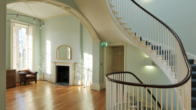 Dining Room for drinks reception with open fireplace and view of the spiral staircase with lots of natural daylight Clissold House Christmas Party N16