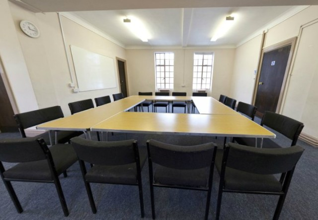 Artists Room set up in a u-shape for a meeting with natural daylight and a whiteboard on the wall Conway Hall Venue Hire WC1