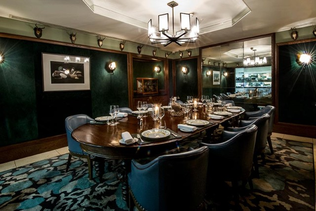 View of Chef's table set for a private dinner with smart blue leather chairs and hanging picture frames Corrigan's Mayfair Venue Hire W1