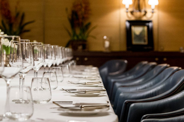 Lindsay Room set for a private dinner with smart blue leather chairs and large wine glasses at each place setting Corrigan's Mayfair Venue Hire W1