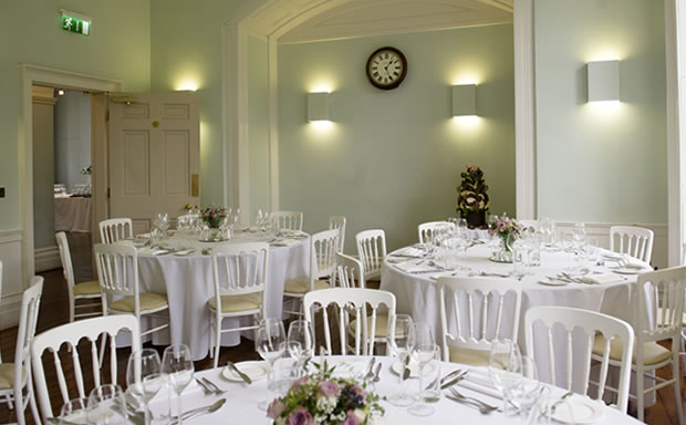 Dining Room set for a dinner with round tables dressed in white table linen and centre pieces Clissold House Christmas Party N16