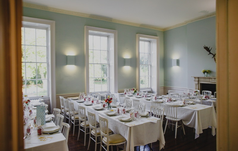 Dining Room set for a wedding breakfast with long tables set out in rows with linen dressed over them and lots of natural daylight Clissold House Venue Hire N16