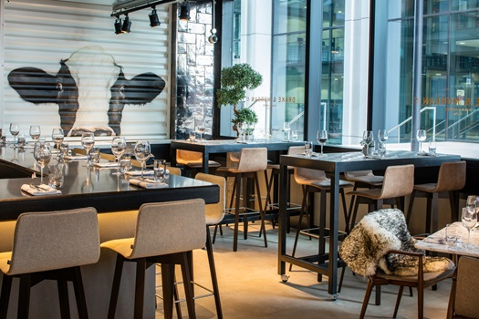 Restaurant with quirky cow paintings on the exposed brick work and formal chairs and tables set for dinner with large floor to ceiling windows for natural daylight Drake & Morgan Kings Cross Venue Hire N1