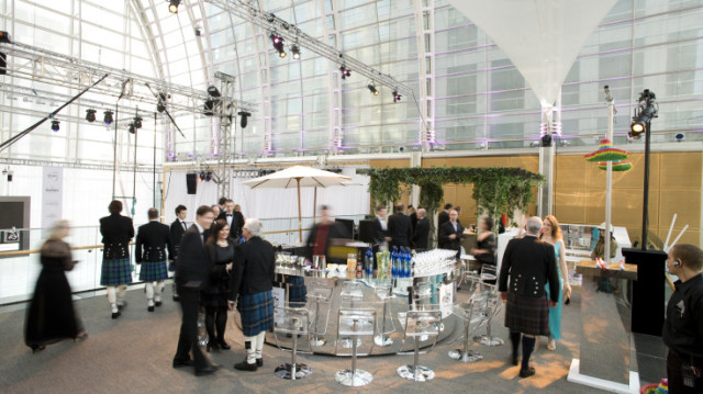 Gallery set for a Scottish gala dinner with a glass pop up bar and light rigged to the ceiling and glass wall with lots of natural light East Wintergarden Venue Hire E14