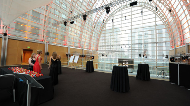 Gallery set for a drinks reception with poseur tables dressed in black linen with light rigging and glass ceiling East Wintergarden Venue Hire E14