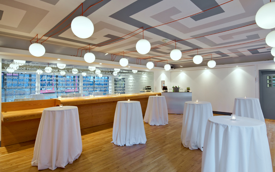 Gallery 3 set for a drinks reception with white table linen draped over poseur tables and natural daylight Whitechapel Gallery Venue Hire E1