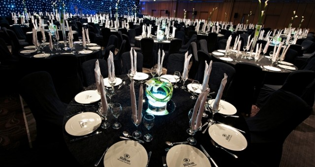 Gateshead Suite set for a large Christmas party with round tables dressed in dark table linen with napkins folded up right and used as centre pieces on the tables Hilton Newcastle Gateshead Christmas Party NE8