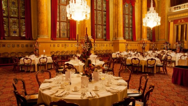 Livery Hall set for a christmas dinner with round tables dressed in white linen and large centre pieces with large chandelier's hanging from grand high ceiling Goldsmiths' Hall Christmas Party EC2