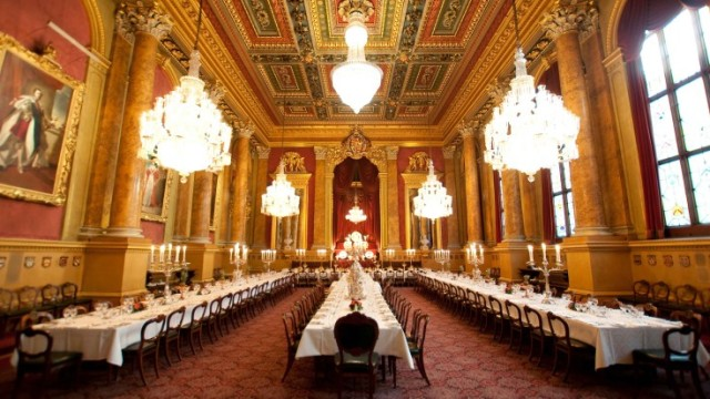 Livery Hall set for a large christmas banquet with 3 long banqueting tables dressed in white linen under the high ceilings and chandeliers Goldsmiths' Hall Christmas Party EC2
