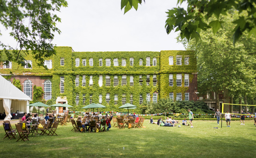York Lawns with guests on outdoor furniture under parasols with a view with the Regents building in the background with ivy over the building and blue summer skies Regent's Conferences and Events Summer Party NW1