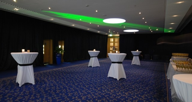 Gateshead Suite Foyer set for a drinks reception with green uplighters shining onto the ceilings with poseur tables draped with white linen Hilton Newcastle Gateshead Christmas Party NE8