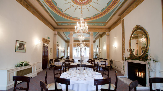 Heggie Room set for dinner with round tables dressed in white linen and a chandelier in the centre of the room 28 Portland Place Venue Hire W1