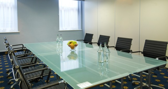 Henley Meeting with long glass table and chairs set around it in boardroom style with natural daylight and water and fruit set out on the table Room Hilton Nottingham Venue Hire NG1
