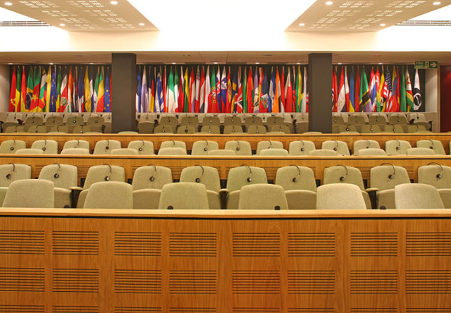 Council Chamber with view of tired seating and international flags hanging in the background ICO Conference Centre Venue Hire W1
