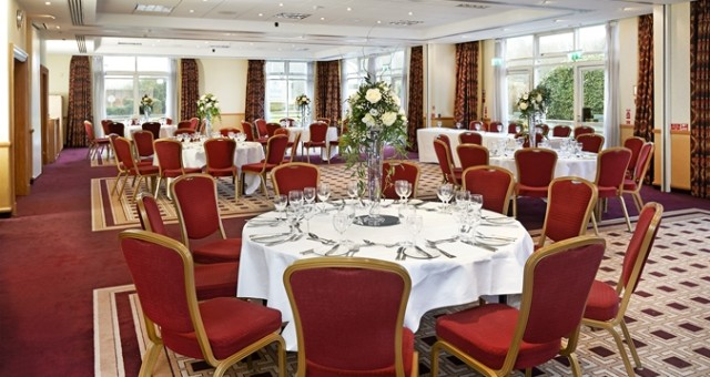 Invicta Suite set for a christmas party with round tables dressed in white linen with floral centre pieces and lots of natural daylight Hilton Maidstone Christmas Party ME14