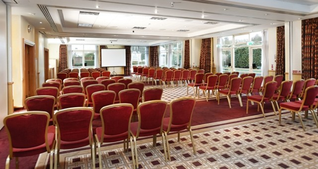Invicta Suite set for a meeting with chairs set in theatre style all facing the front of the room with a large projector screen and lots of natural daylight Hilton Maidstone Venue Hire ME14