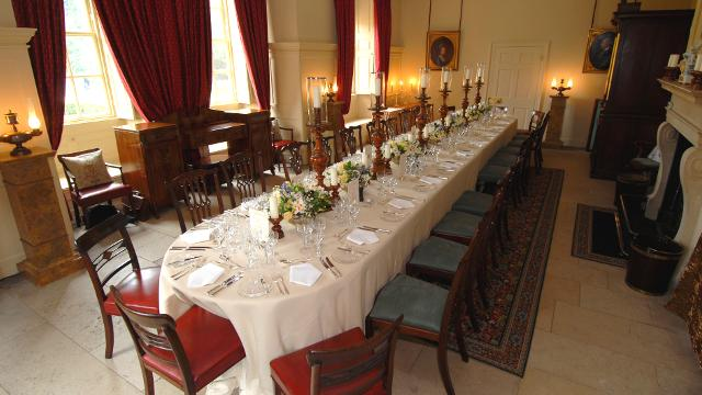 Kings Dining Room set for a private dinner party with a long banqueting table dressed in white linen with floral centre pieces with an open fireplace and grand curtains draped over the windows Kew Palace Venue Hire TW9