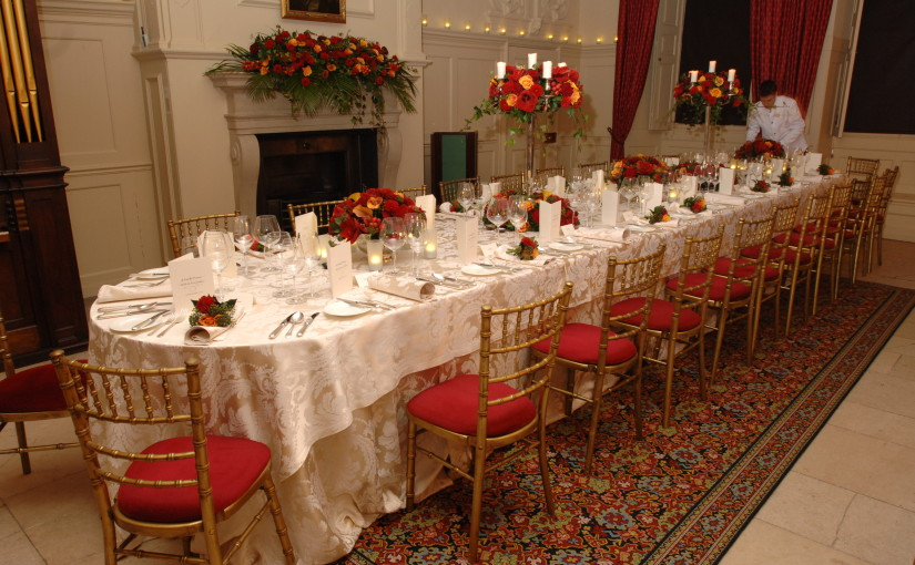 Kings Dining Room set for a private Christmas dinner with a long banqueting table dressed in white linen and winter foliage decorating the table and open fireplace Kew Palace Christmas Party TW9