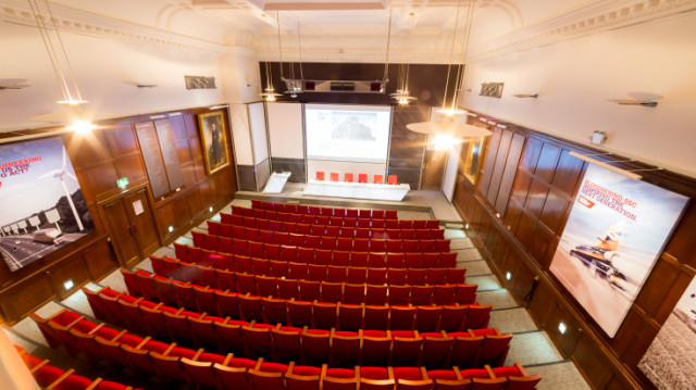 Lecture Theatre set in a tiered theatre style with formal red chairs a stage with lecture and presentation facilities One Birdcage Walk Venue Hire SW1