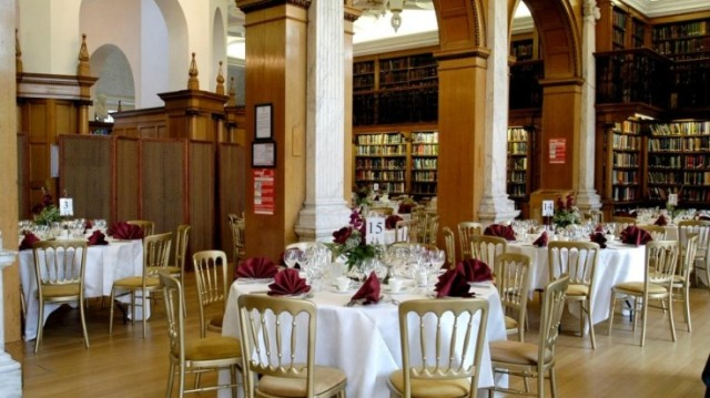 Library set for a dinner with round tables set for dinner with floral centre pieces with surrounding library walls One Birdcage Walk Venue Hire SW1