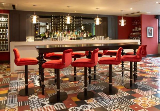 Nicholson's Bar and Diner Restaurant view with of the bar with lots of spirits bottles with high tables and formal chairs Hilton Nottingham Venue Hire NG1