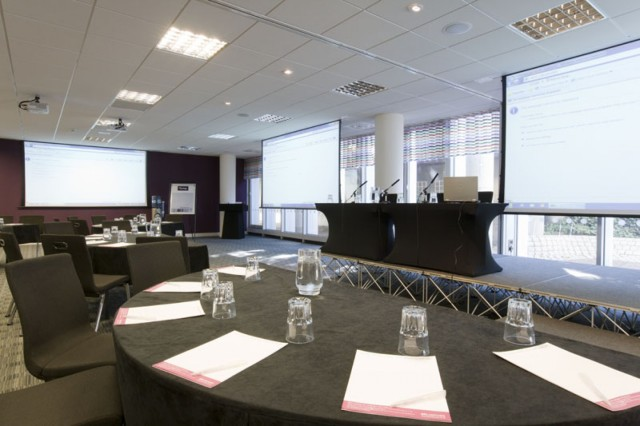 Meeting Room set for a conference events with stage and mircophone as well as presentation facilities with half moon tables set in cabaret style One Drummond Gate Venue Hire SW1