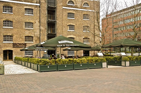 Browns West India Quay Venue Hire E14. Views of exterior of venue, showing terrace with umbrella and chairs with bushes around to make space more enclosed to bar.