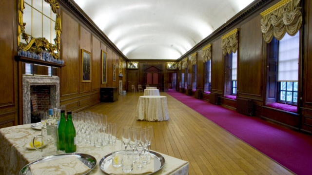 Queens Gallery set for a drinks reception with grand linen draped over centre poseur table and drinks station with champagne glasses, windows against one side of the wall for natural daylight Kensington Palace Venue Hire W8