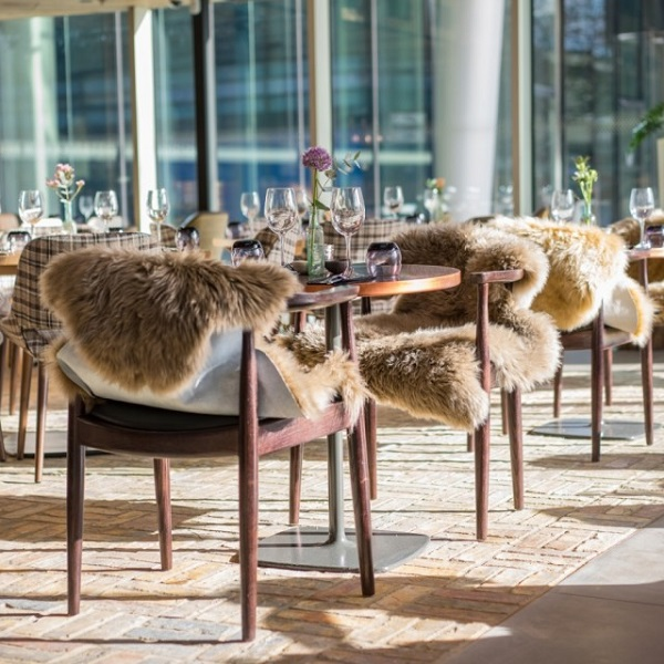 Refinery Regents Place Christmas Party NW1. Tables and chairs with furr thrown on chairs.