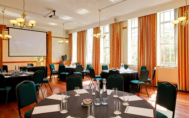 Tuke Common Room in cabaret style for a conference with large floor to ceiling windows and lots of natural daylight Regent's Conferences and Events Venue Hire NW1