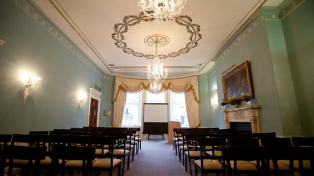 Sainsbury Room set for a meeting with chairs arranged in theate style and presentation facilities at the front of the room with lots of natural daylight 28 Portland Place Venue Hire W1