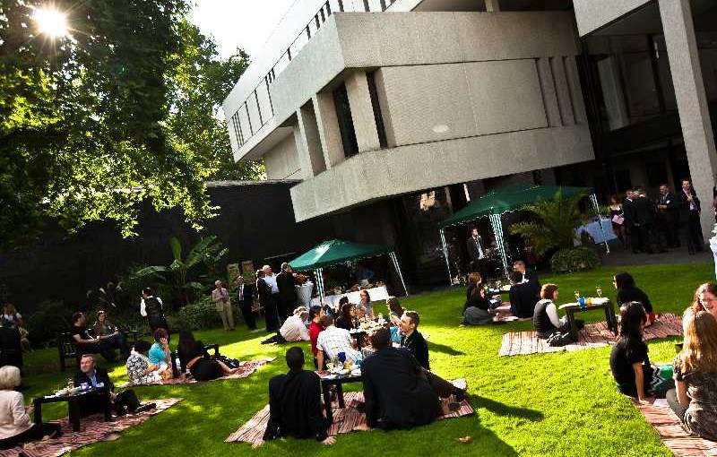 Garden Party with view of the heritage building and parasols set up on the lawn Royal College of Physicians Venue Hire NW1